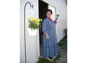 Sarah Uthoff dressed as Laura Ingalls Wilder in front of her Laura building