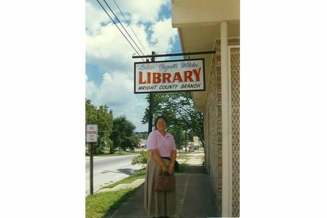 Sarah in an incredibly pretty outfit standing under the Mansfield library sign.