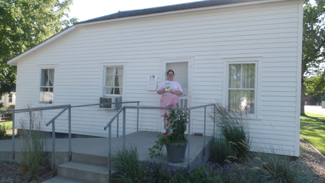 Sarah holding Little House book on the cement porch in front of Surveyor's House