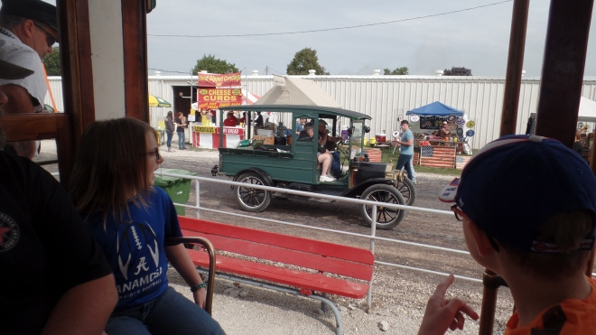 People riding on a trolley see a restored truck
