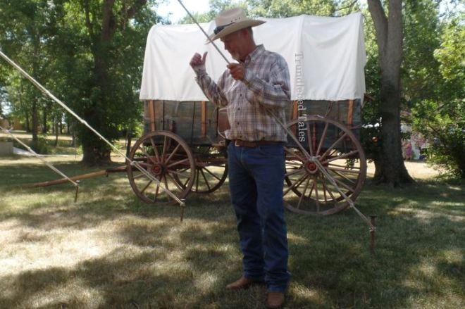 Man in front of covered wagon