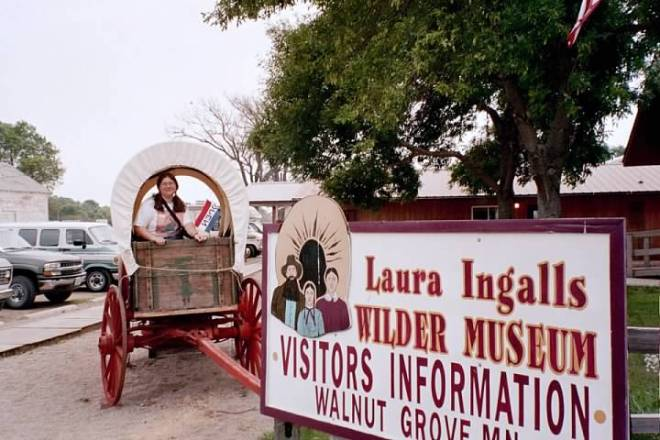 Me in covered wagon by Walnut Grove Museum Sign
